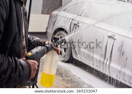 luxury black car washing process when the worker holding spray foam gun and standing next to the car fully covered with white car foam splashes - stock photo