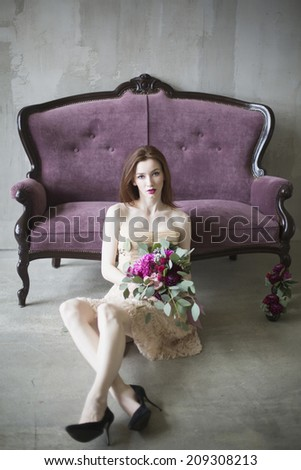 Luxury bride in a pink dress with a wedding bouquet in the wine color, on the couch - stock photo