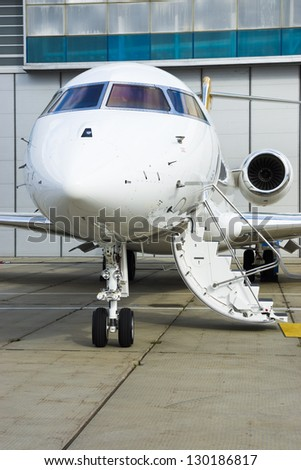 Luxury Business Private Jet plane at airfield toned in blue - stock photo