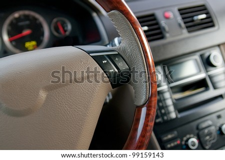 luxury car interior with wooden steering wheel close up - stock photo