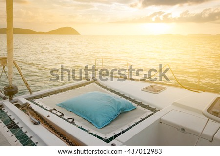 Luxury catamaran yacht deck. Blue and white stripes  mattress for sunbathing during sunset in the evening, with light effect - stock photo