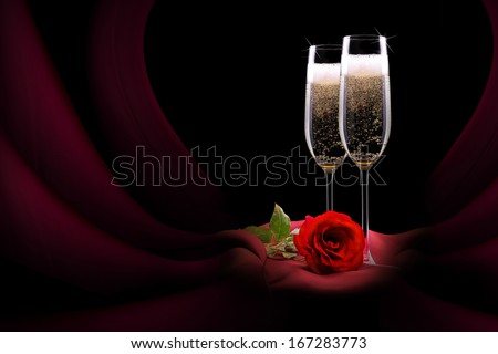 luxury champagne glass with red silk and flower on black background - stock photo