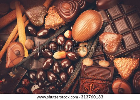 Luxury chocolate background close up. Candies Chocolate vintage style. Delicious assortment of white, dark, milk chocolate bonbon with nuts, vanilla and cinnamon. Belgium chocolate - stock photo