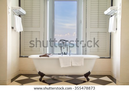 Luxury classic bathtub in bathroom with relaxing ambient and window  with scenic sea view - stock photo