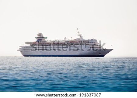 Luxury cruise ship sailing from port - stock photo