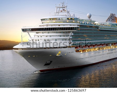Luxury cruise ship sailing from port on sunrise - stock photo