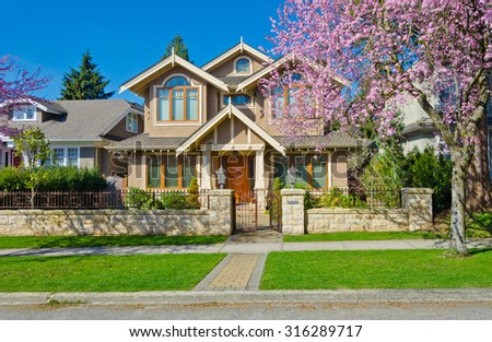 Luxury custom made house at sunny day, cherry blossom, spring time  in Vancouver, Canada. - stock photo