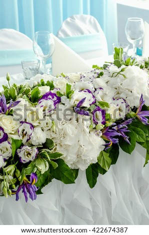 Luxury decoration with lush leaves, white hydrangea, delicate cream roses, purple eustoma, blue iris on a wedding table in banquet restaurant. Style summer sea marriage concept. Floral arrangement - stock photo