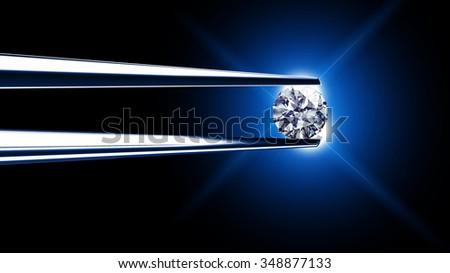 Luxury diamond in tweezers closeup  - stock photo