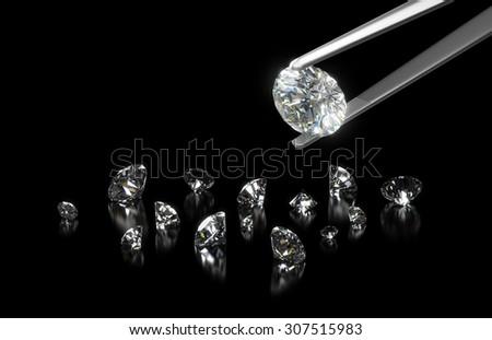 Luxury diamond in tweezers closeup with dark background - stock photo
