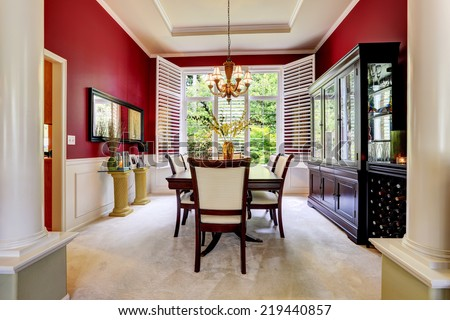 Luxury dining room with bright red wall and white french window. - stock photo