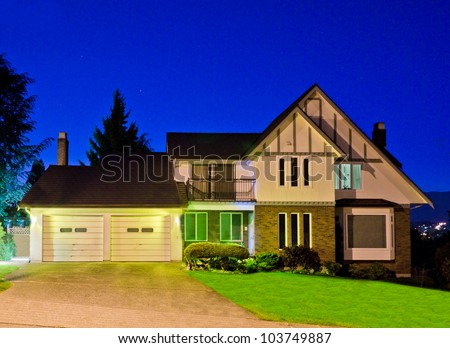 Luxury double garage doors home at dick       ( night, dawn ) time . - stock photo