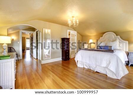 Luxury elegant gold bedroom interior with white bedding and hardwood floor. - stock photo