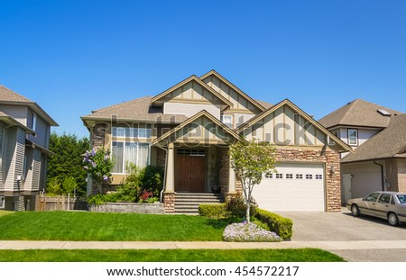 Luxury family house with car parked on concrete driveway. Residential house with landscaped front yard on blue sky background - stock photo
