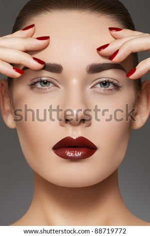 Luxury fashion style, manicure, cosmetics and make-up. Dark lips makeup & nails polish. Close-up portrait of female model with red lipstick, fingernails and clean skin - stock photo
