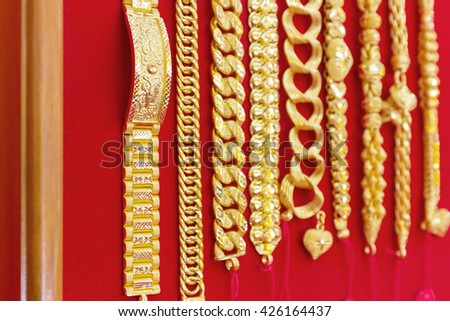 Luxury gold bracelets on red flannel, gold ornament, gold bar, gold accessory, gold accessories, gold bracelet, gold ring, gold necklace, gold asian, gold shop, gold golden background, gold pendant. - stock photo