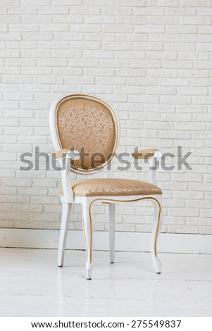 Luxury Golden Vintage Chair On Brick Wall. - stock photo