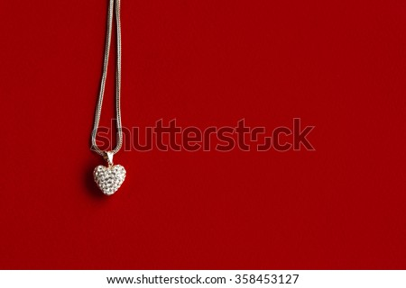 luxury heart necklace with stylish diamonds on red background, present and love concept, valentine's day - stock photo