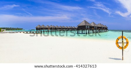 luxury holidays in Maldives island, panoramic view with water bungalows - stock photo
