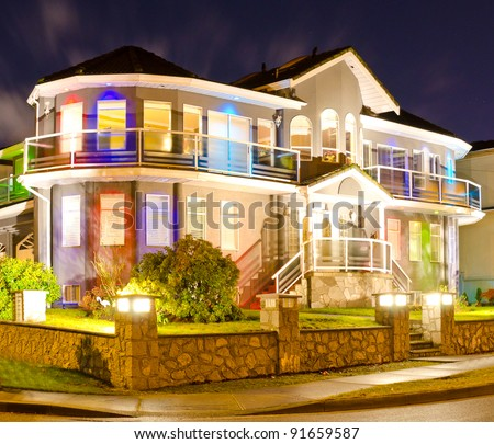 Luxury home exterior in the night time illuminated with lights - stock photo