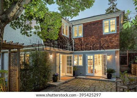 Luxury Home Exterior with wooden shingles house, garden, stone floor and wooden deck at twilight. - stock photo