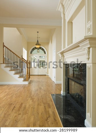 Luxury Home Foyer Door Staircase and Fireplace - stock photo