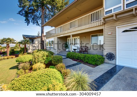 Luxury home with well kept lawn, and two garage spaces. - stock photo