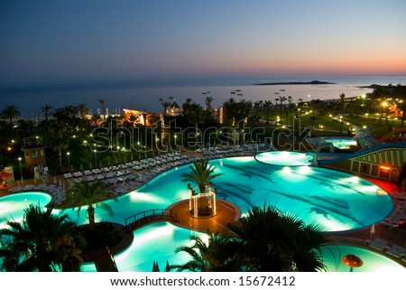 luxury hotel with pool at night - stock photo