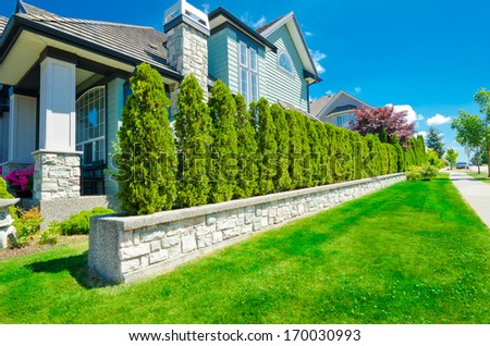 Luxury house behind the nicely trimmed green fence  at the empty street in the suburbs of Vancouver, Canada. Keeps privacy and security. Landscape trimming design. - stock photo