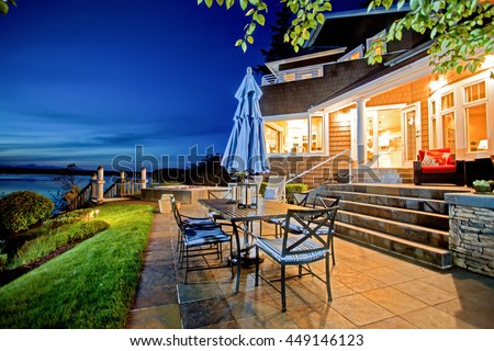 Luxury house exterior with impressive water view and cozy patio area. Summer evening. - stock photo