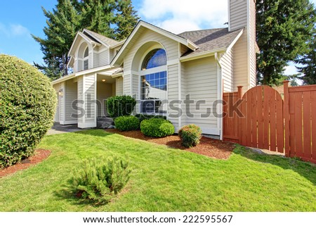 Luxury house exterior with tile roof and big arch windows. Front yard landscape design - stock photo