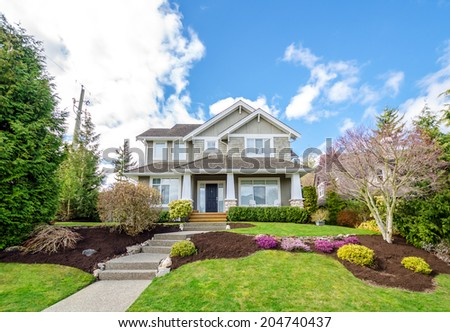 Luxury house with beautiful landscaping on a sunny day. Home exterior design. - stock photo