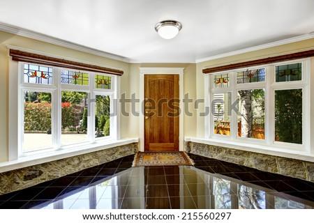 Luxury interior. Foyer with black shiny tile floor, large windows  with stone windowsill base trim - stock photo