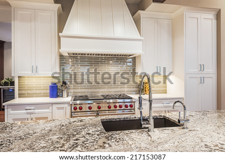 Luxury Kitchen Detail: Island, Counter-top, Sink, Cabinets, Range, and Oven - stock photo
