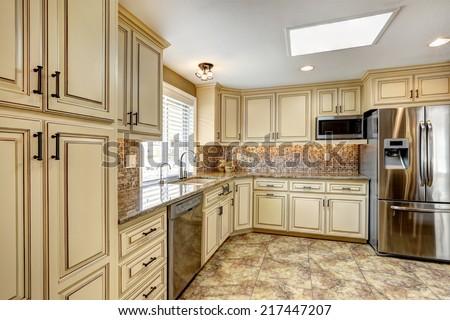 Luxury kitchen interior in light beige color with back splash trim and tile floor - stock photo