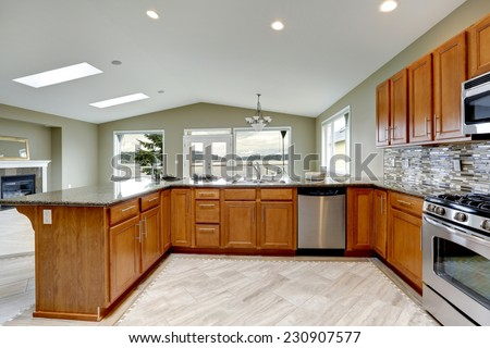 Luxury kitchen room with bright brown cabinets, mosaic backsplash trim and streel appliances. - stock photo