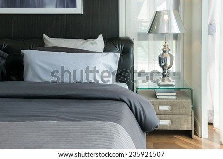 luxury lamp and books on bedside table in bedroom  - stock photo