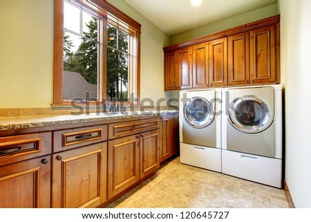 Luxury laundry room with wood cabinets and tile floor. - stock photo