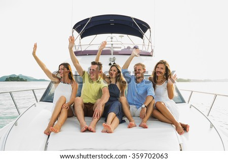 Luxury life . Group of young beautiful people smiling and showing hello by hands on the yacht - stock photo
