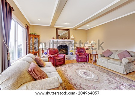 Luxury living room interior with brick background fireplace, hardwood floor and rug. Furnished with comfortable sofa and leather armchairs - stock photo