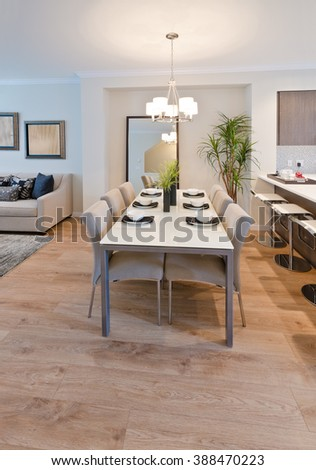 Luxury living suite : nicely decorated dining table and the kitchen and sofa at the back. Interior design. - stock photo