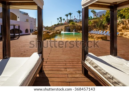 Luxury loungers and Swimming pool with artificial waterfall - stock photo