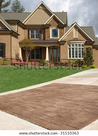 Luxury Model Home Exterior with stone driveway - stock photo