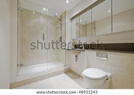luxury modern en-suite bathroom with floor to ceiling marble tiles - stock photo