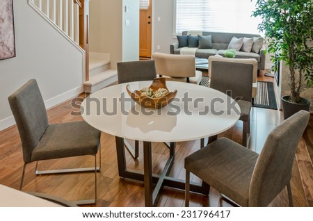 Luxury modern living suite : dining  table with decorative wooden vase and living room  at the back Interior design of brand new house. - stock photo