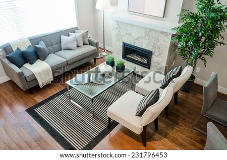 Luxury modern living suite, room with sofa and chairs and nicely decorated coffee table with vase.  View from above. Interior design of a new house. - stock photo