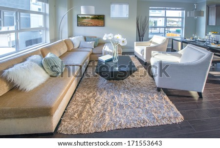 Luxury modern living suite, room with sofa and chairs and the dining table at the back.  Interior design of a brand new townhouse. - stock photo