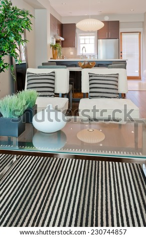 Luxury modern living suite : two modern chairs with nicely decorated coffee table and dining room and kitchen at the back Interior design of a brand new house. Vertical. - stock photo