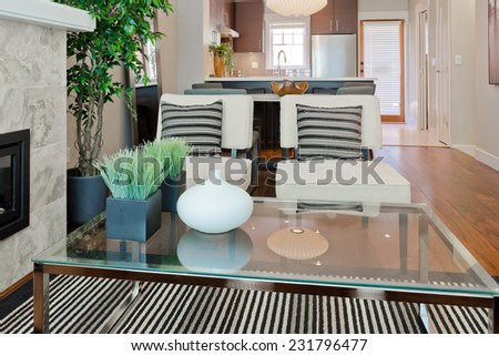 Luxury modern living suite : two modern chairs with nicely decorated coffee table and dining room and kitchen at the back Interior design of a brand new house. - stock photo