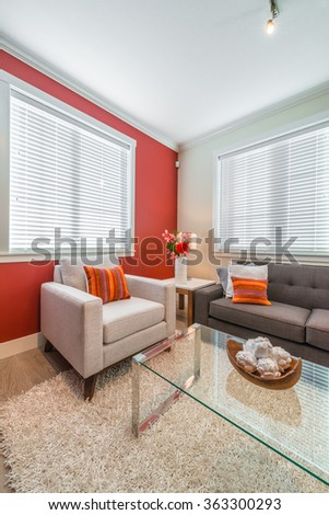 Luxury modern living suite with red color walls, room with sofa and chairs and nicely decorated coffee table with vase.  Interior design. Vertical. - stock photo